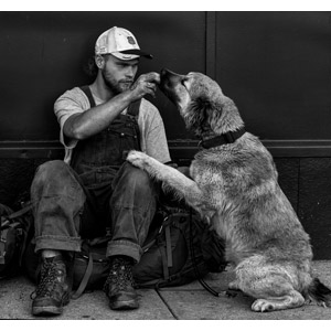 フリー写真, 人物, 男性, 外国人男性, サロペット, 帽子, キャップ帽, 人と動物, 動物, 哺乳類, 犬(イヌ), モノクロ, 舐める(動物), ホームレス, 貧困