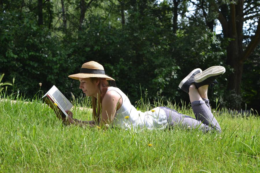 フリー写真 草むらに腹ばいになって本を読む外国人女性