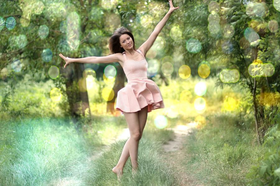 フリー写真 光の玉ボケと手を広げて踊る外国人女性