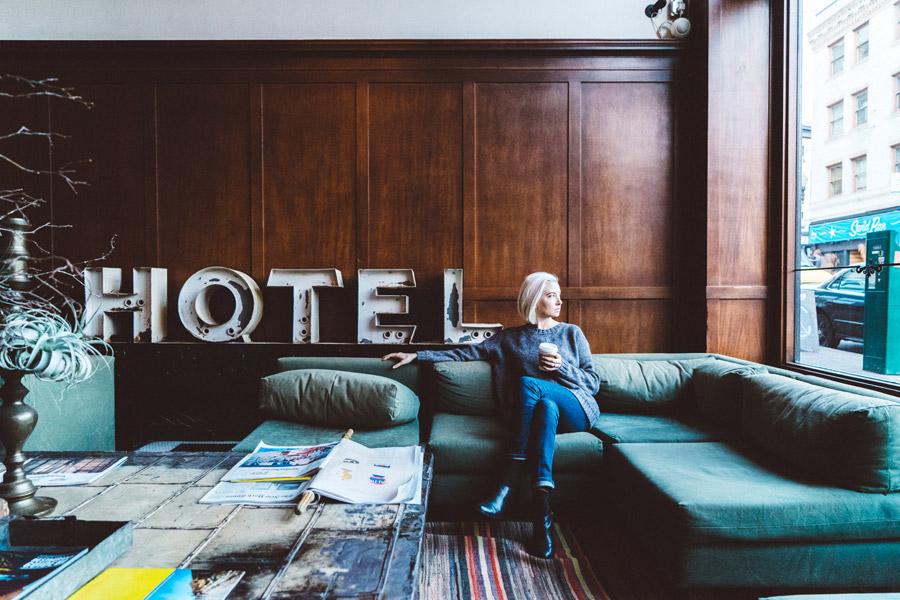 フリー写真 ホテルのロビーにあるソファーに座る外国人女性