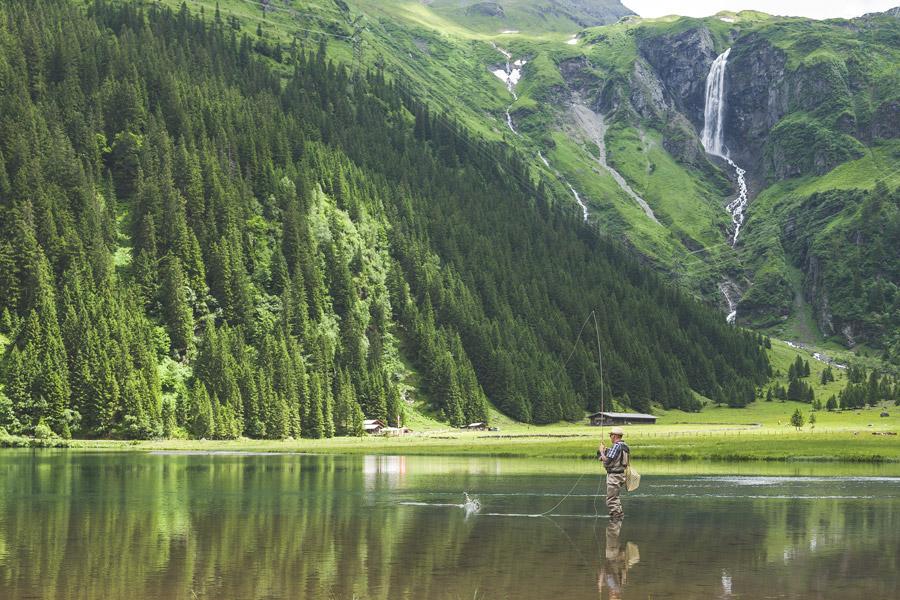 フリー写真 山と滝と湖で魚釣りしている釣り人