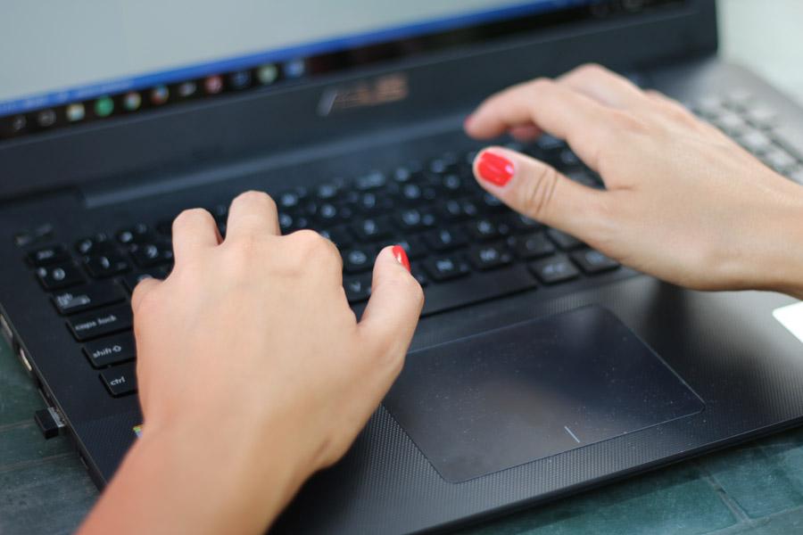 フリー写真 ノートパソコンのキーボードを叩く女性の手