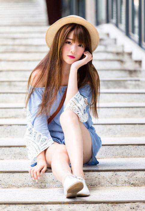 フリー写真 階段に頬杖をついて座る女性のポートレイト
