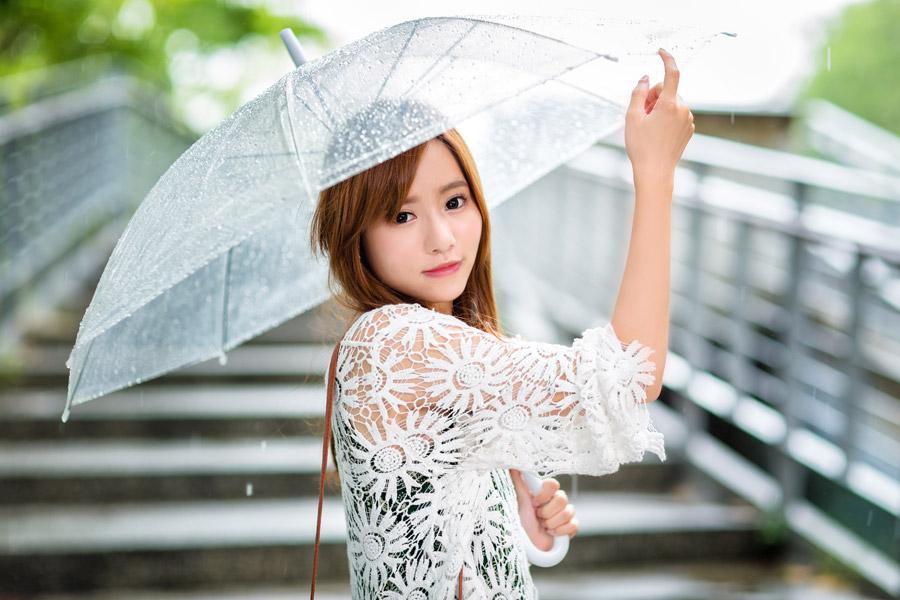 フリー写真 雨の中で傘を差している女性のポートレイト