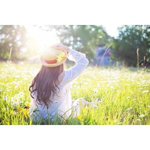 フリー写真, 人物, 女性, 帽子, 麦わら帽子, 頭に手を当てる, 座る(地面), 草むら, 人と花, 人と風景, 太陽光(日光), 女性(00260)