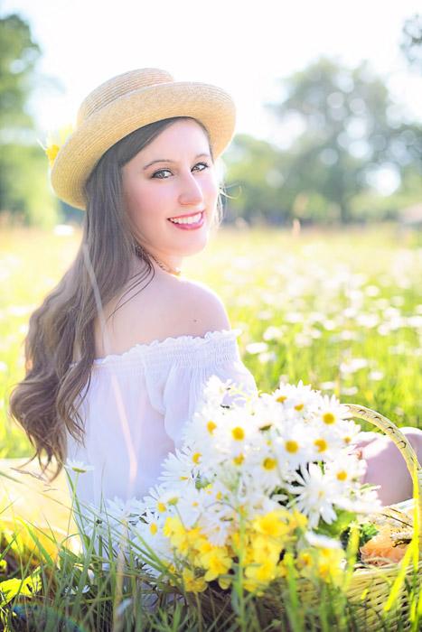 フリー写真 ヒナギクの花と草むらに座る外国人女性