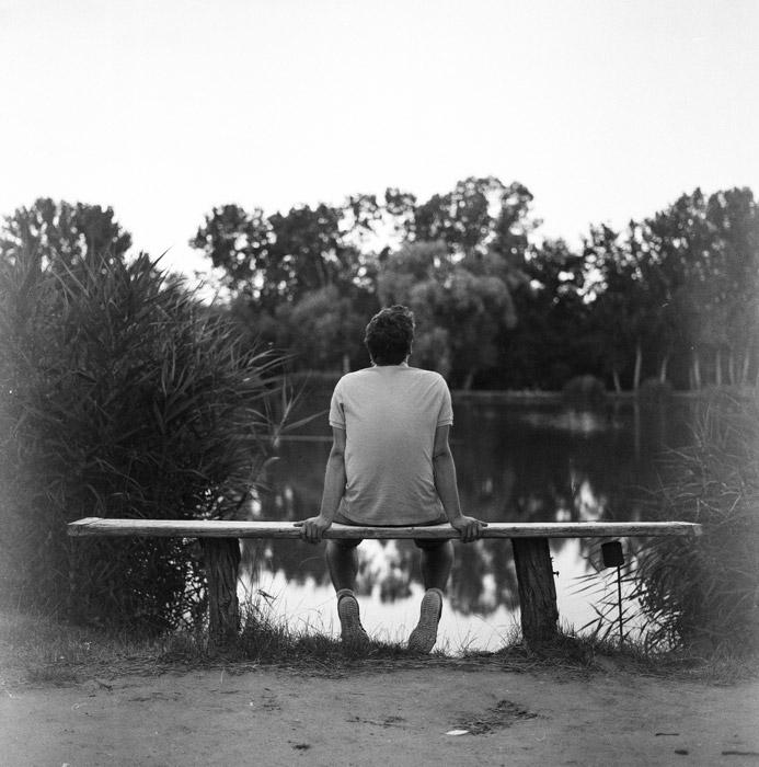 フリー写真 池の前のベンチに座る男性の後ろ姿