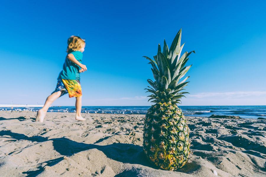 フリー写真 パイナップルとビーチを走る男の子