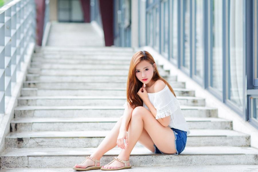 フリー写真 サンダルを履いて階段に座っている女性