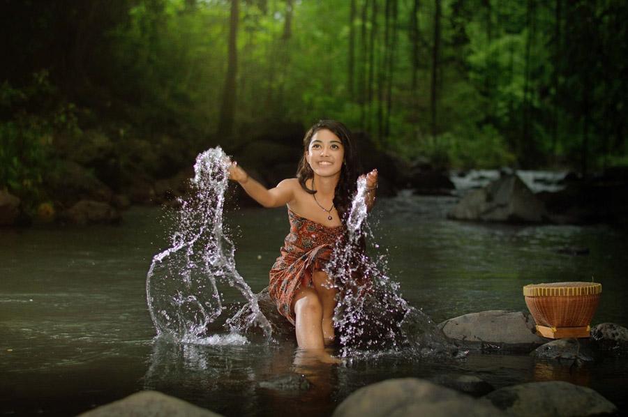 フリー写真 川の中にある石に座って水しぶきをあげる女性