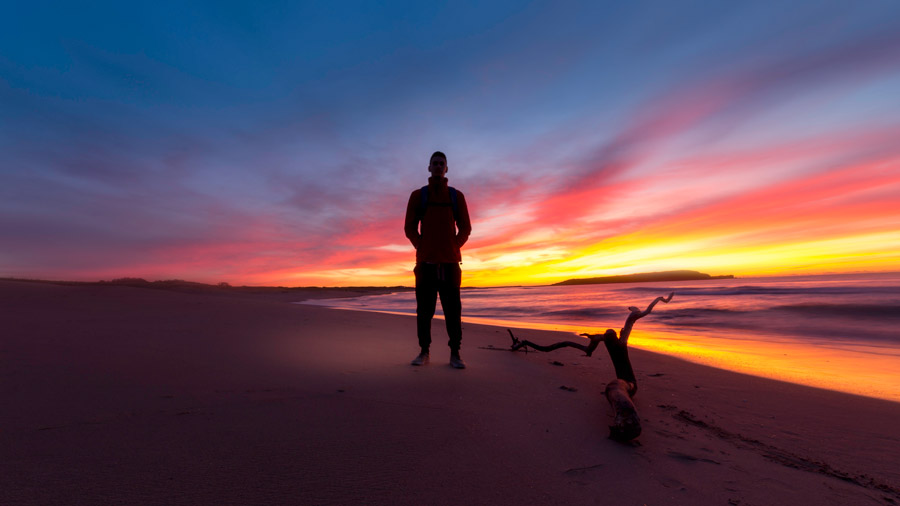 フリー写真 夕暮れのビーチに立つ人物
