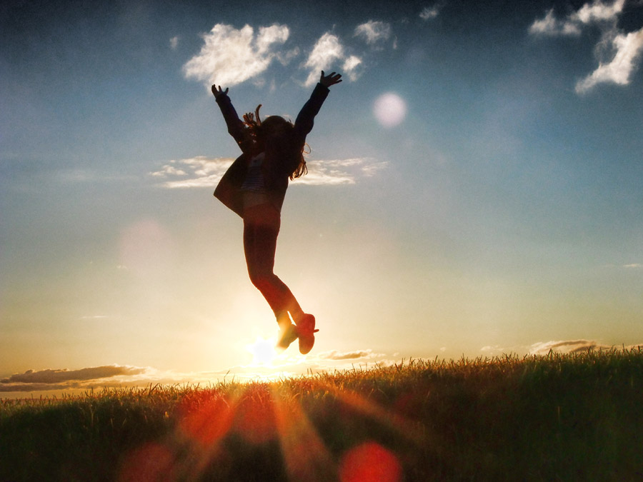 フリー写真 「やったー!」とジャンプする女性と夕日