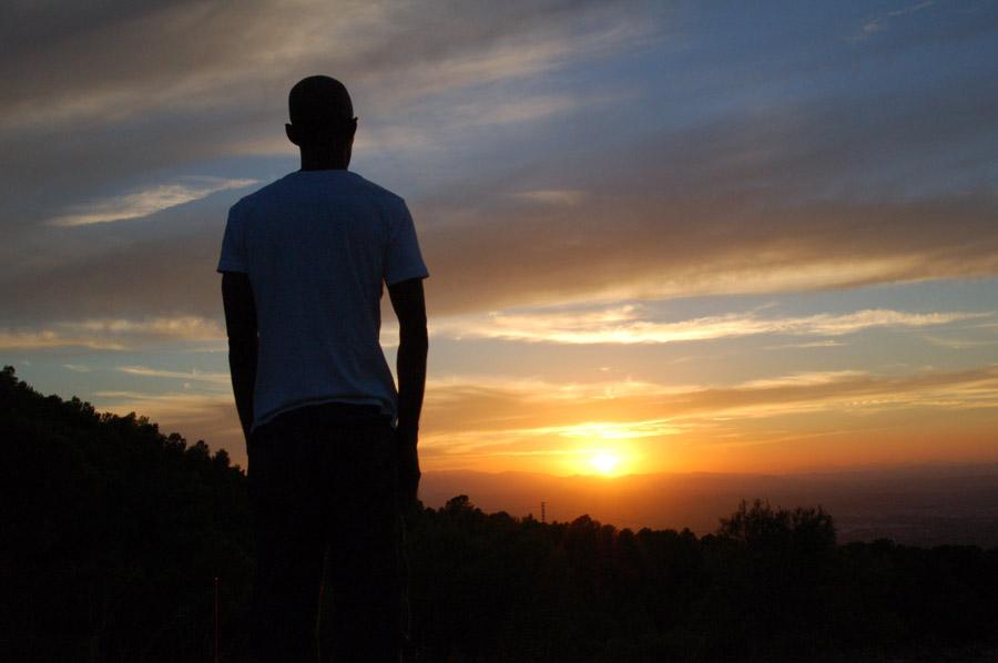 フリー写真 沈みゆく太陽を見つめる男性の後ろ姿