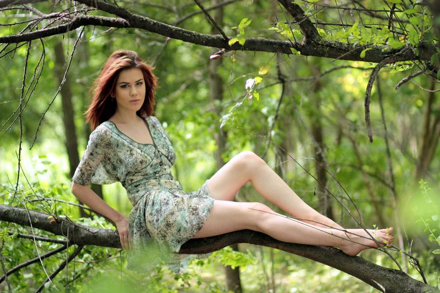 フリー写真 森の木の枝の上に座る外国人女性