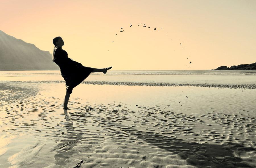 フリー写真 ビーチの砂を蹴り上げる少女