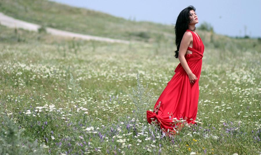 フリー写真 赤いドレス姿で草むらに立つ外国人女性