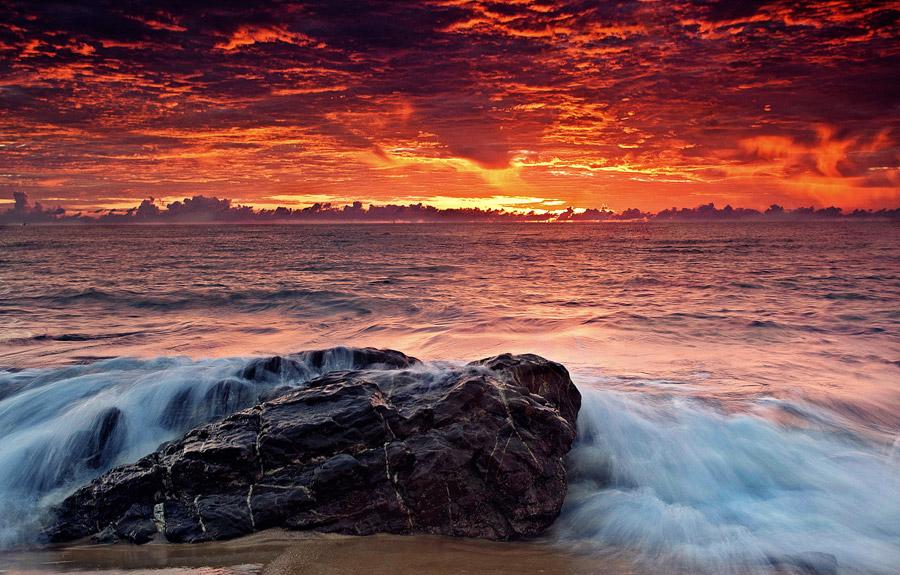 フリー写真 朝焼けの海と浜辺の岩の風景