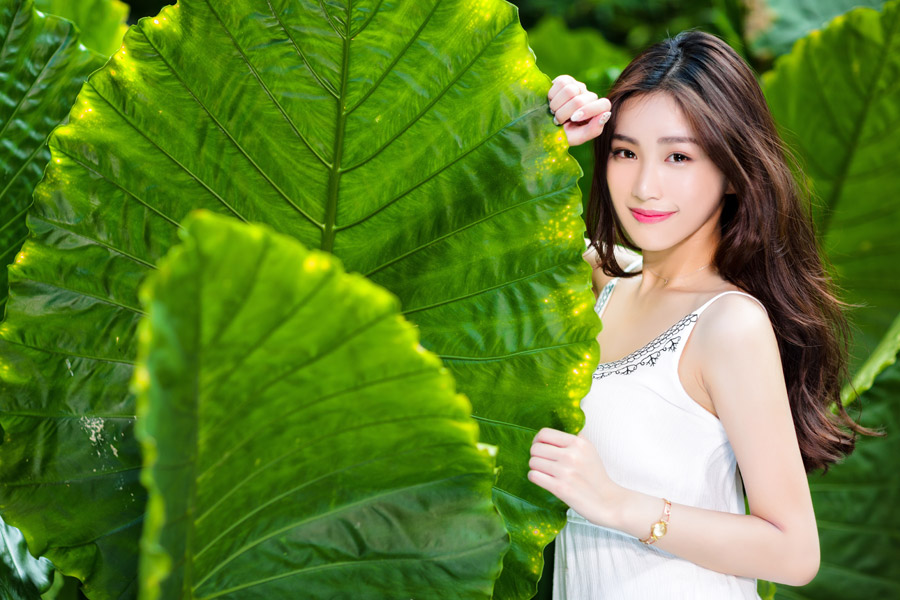 フリー写真 大きな葉っぱの側にいる女性のポートレイト