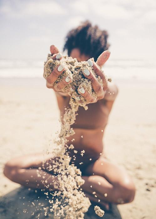 フリー写真 女性の手からこぼれ落ちるビーチの砂