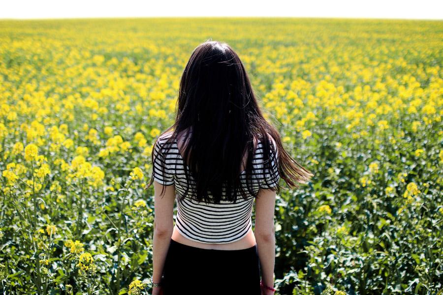 フリー写真 菜の花畑の前に立つ女性の後ろ姿