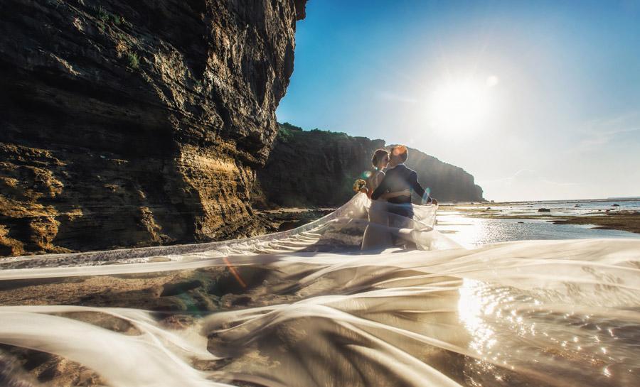 フリー写真 海岸でベールを広げる新郎新婦