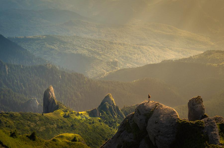 フリー写真 山と薄明光線と岩山の頂に立つ女性登山者