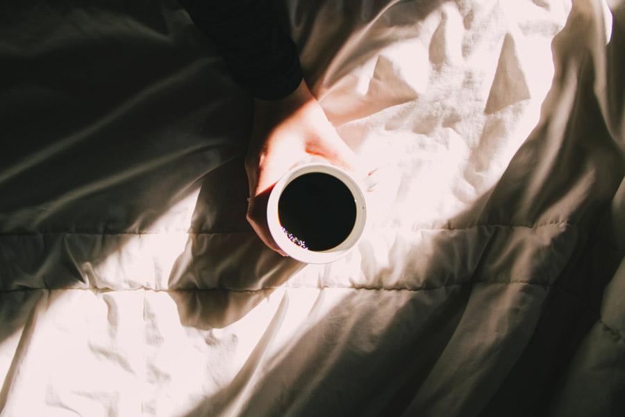 フリー写真 ベッドの上のコーヒーと手