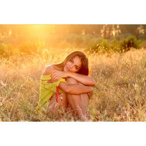フリー写真, 人物, 女性, 外国人女性, 女性(00234), ルーマニア人, 座る(地面), 草むら, 夕暮れ(夕方), 太陽光(日光), 膝を抱える