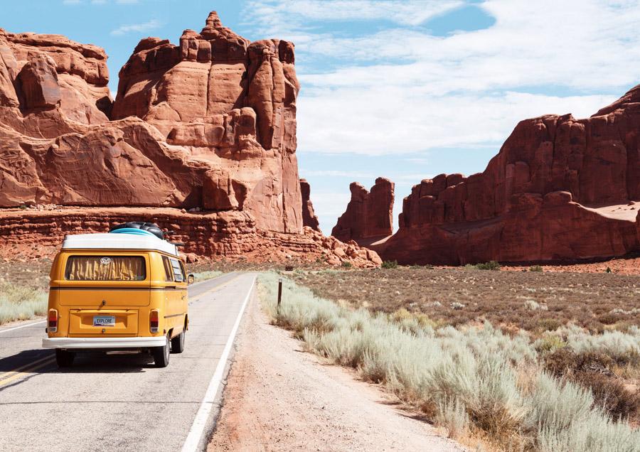 フリー写真 アーチーズ国立公園の岩山と道路を走る車