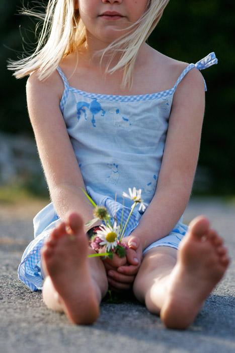 フリー写真 花を持って地面に座っている外国の女の子