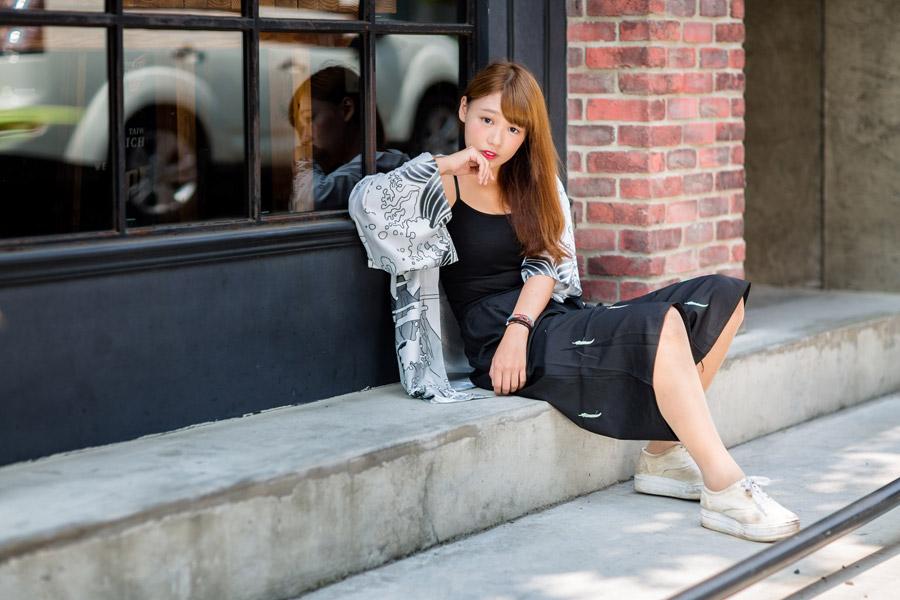 フリー写真 通りの脇に座り込む女性