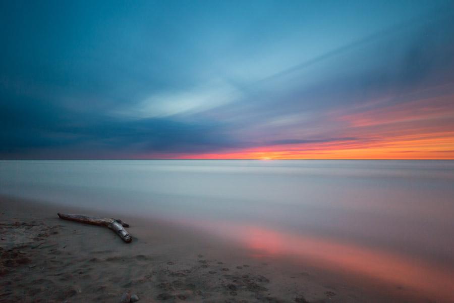 フリー写真 流木と夕暮れの砂浜と海の風景