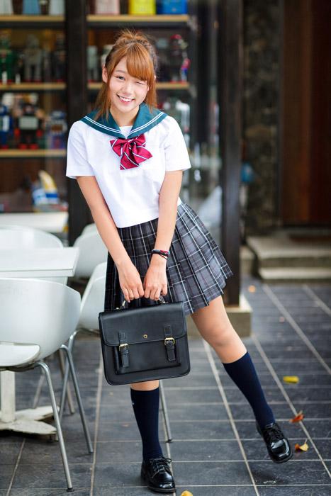フリー写真 片足で立ちながらウインクしている女子高生