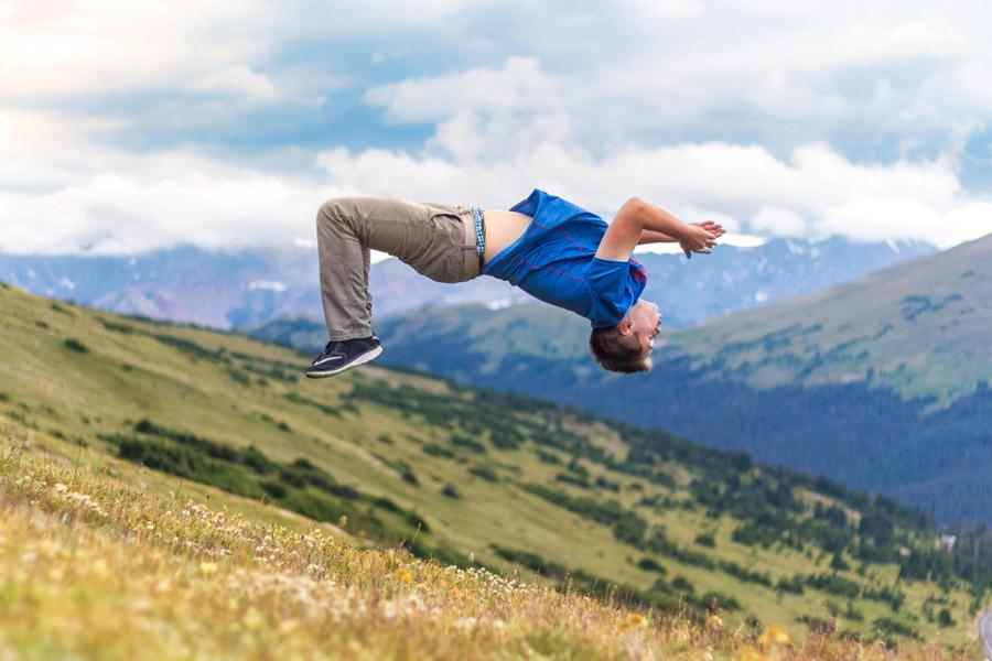 フリー写真 山の斜面でバク転する外国人男性