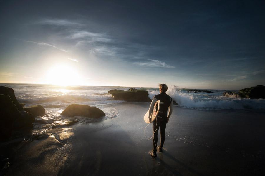 フリー写真 サーフボードを担いで夕日を眺めるサーファー