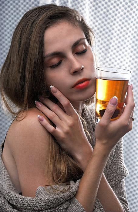 フリー写真 目を閉じながらコップに頬に当てる外国人女性