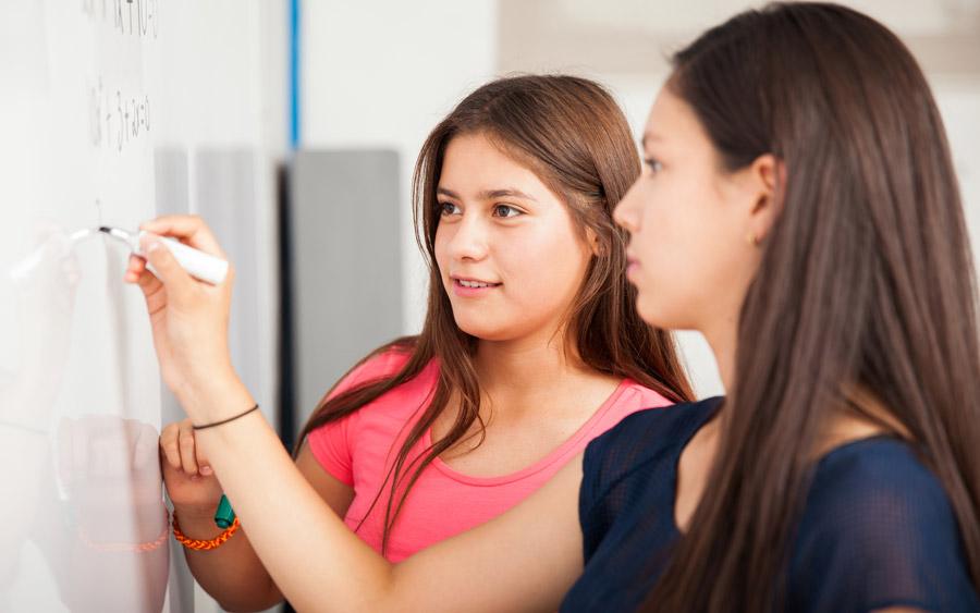 フリー写真 ホワイトボードに数式を書く二人の女子高生