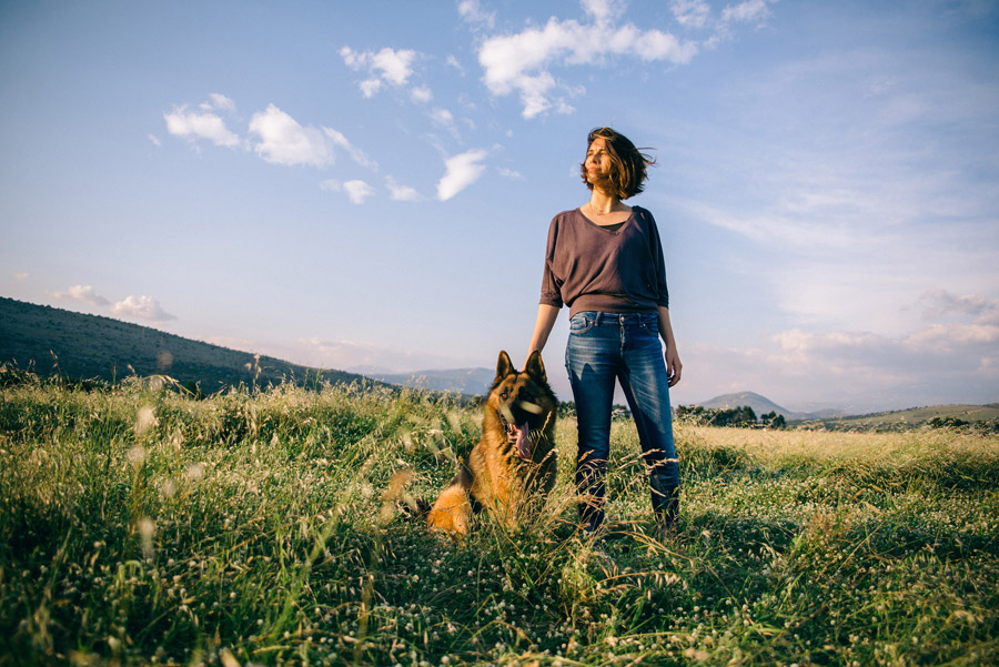 フリー写真 草むらにいる外国人女性と犬