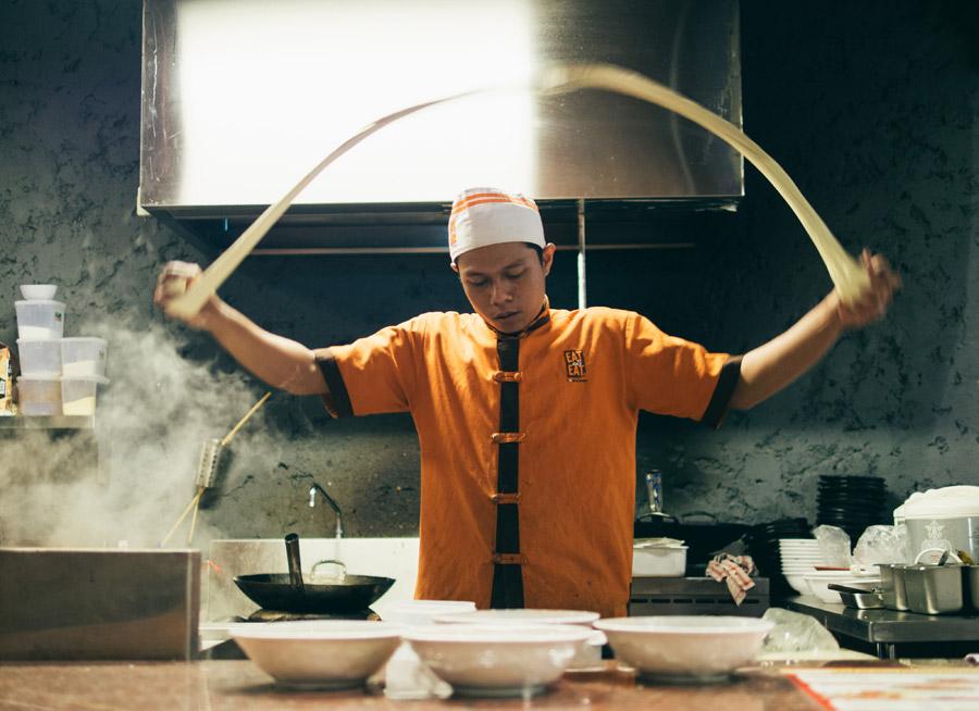 フリー写真 厨房で麺を打つ中華の料理人