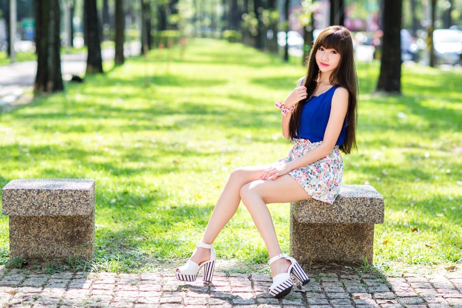 フリー写真 公園の石のベンチに座る女性のポートレイト
