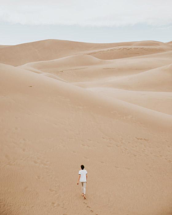 フリー写真 砂漠を歩く人物の後ろ姿