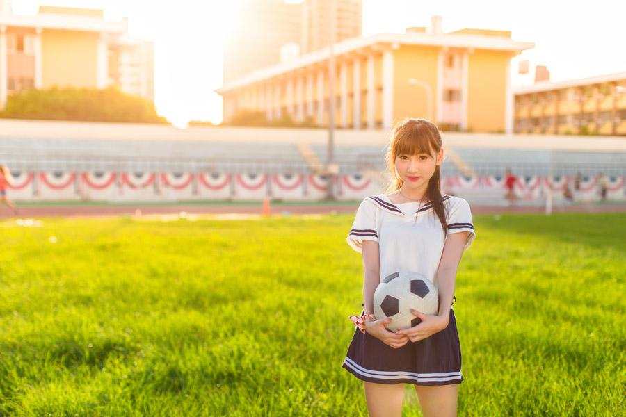 フリー写真 芝生の上でサッカーボールを抱える女子高生