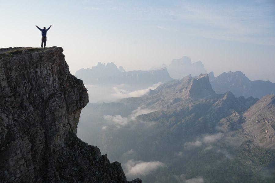 フリー写真 絶壁の上で歓喜する人物とドロミテ山脈の風景