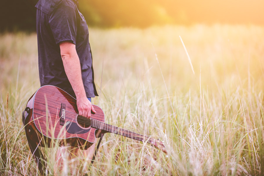 フリー写真 草むらでギターを持つ人物