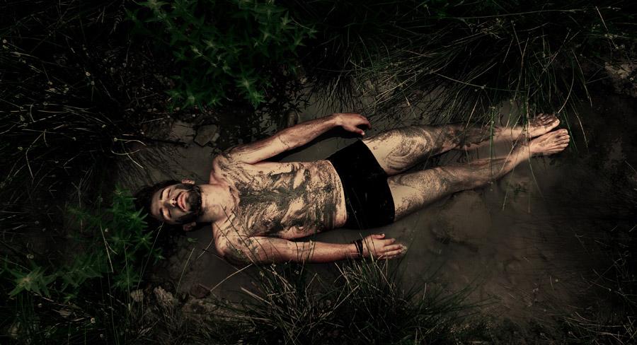 フリー写真 泥だらけで地面に寝転ぶ外国人男性