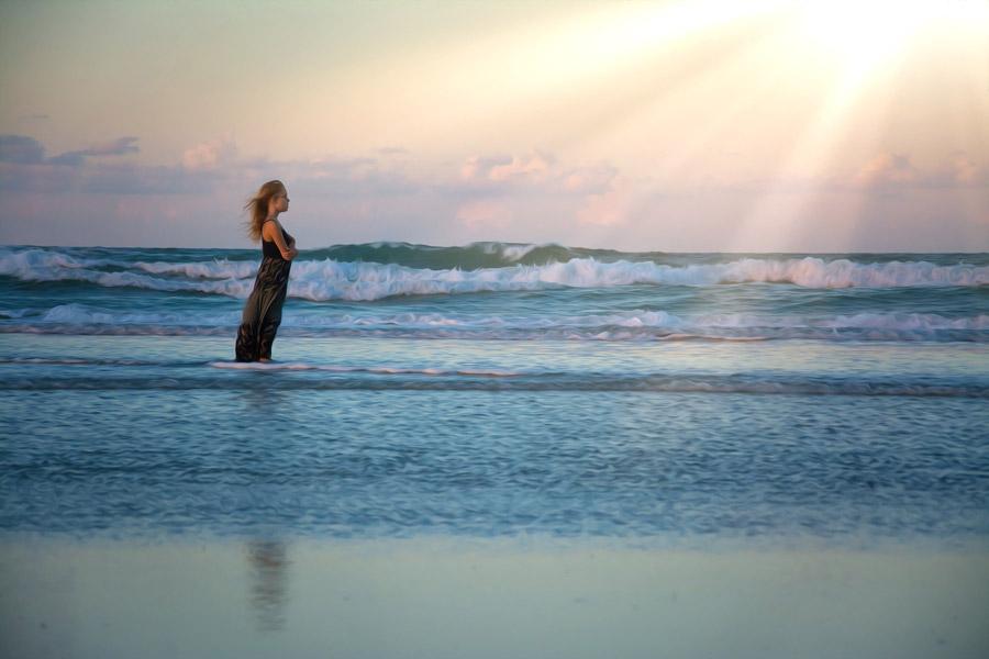 フリー写真 太陽の光と波打ち際に立つ女の子