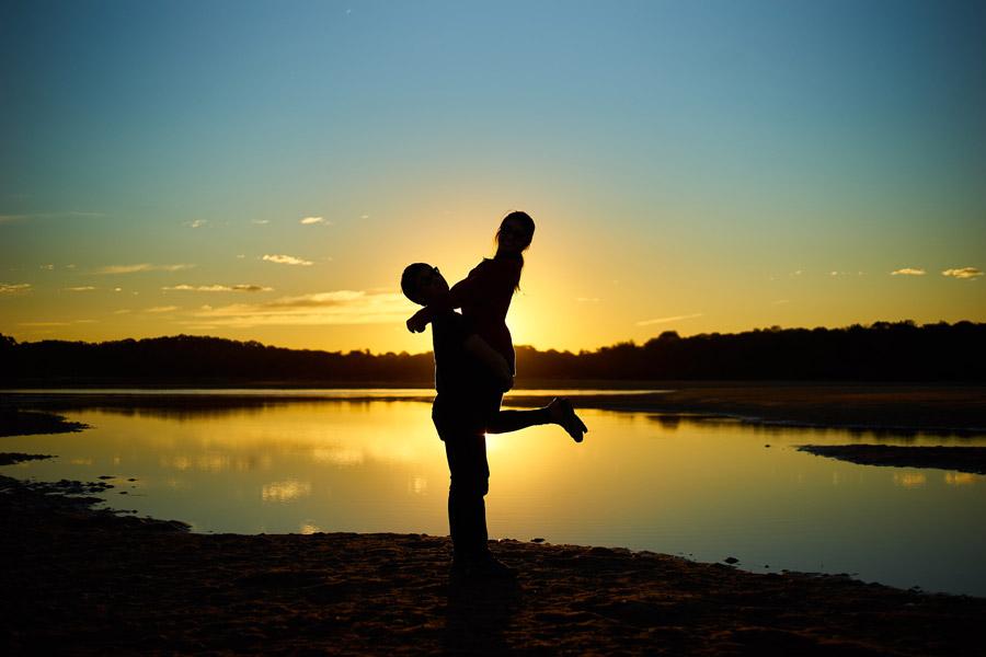 フリー写真 夕日と彼女を抱き上げる彼氏