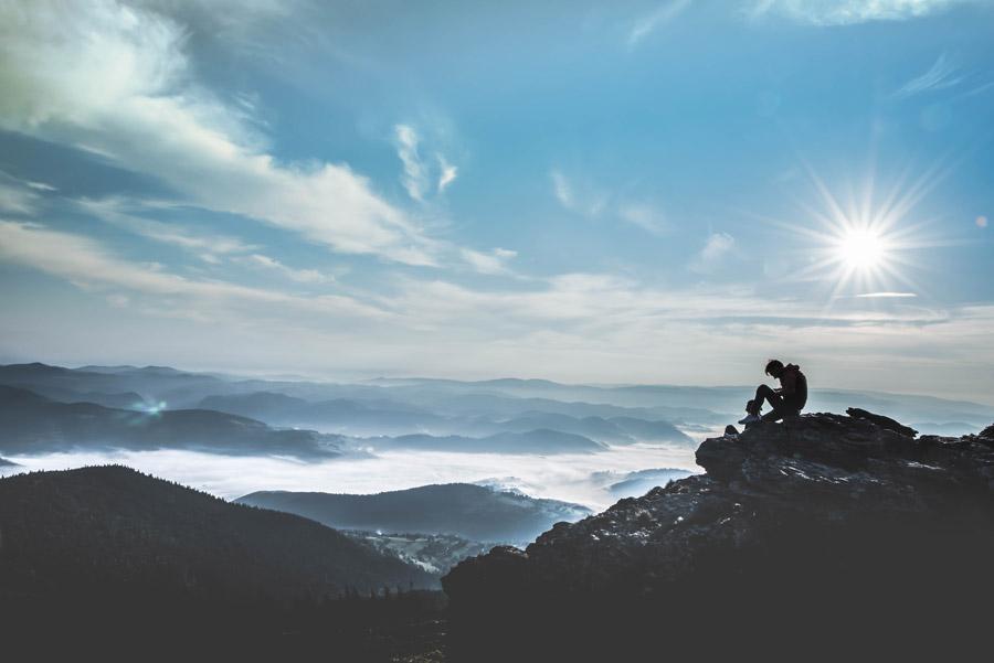 フリー写真 太陽の光と山と雲海の風景と岩に座る登山者