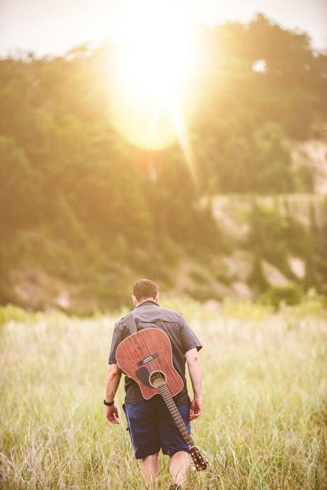 フリー写真 ギターを背負って草むらを歩く男性