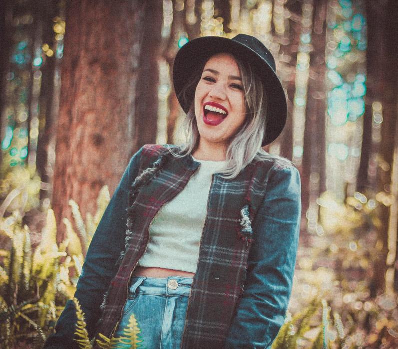 フリー写真 森の中で帽子を被って笑う外国人女性